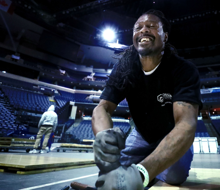 <strong>Joseph Woods, a contractor for the conversion team at the FedExForum, installs the AAC Tournament court at the FedEx Forum. The University of Memphis will kick off their tournament schedule playing Tulane on Thursday, March 14.</strong> (Houston Cofield/Daily Memphian)