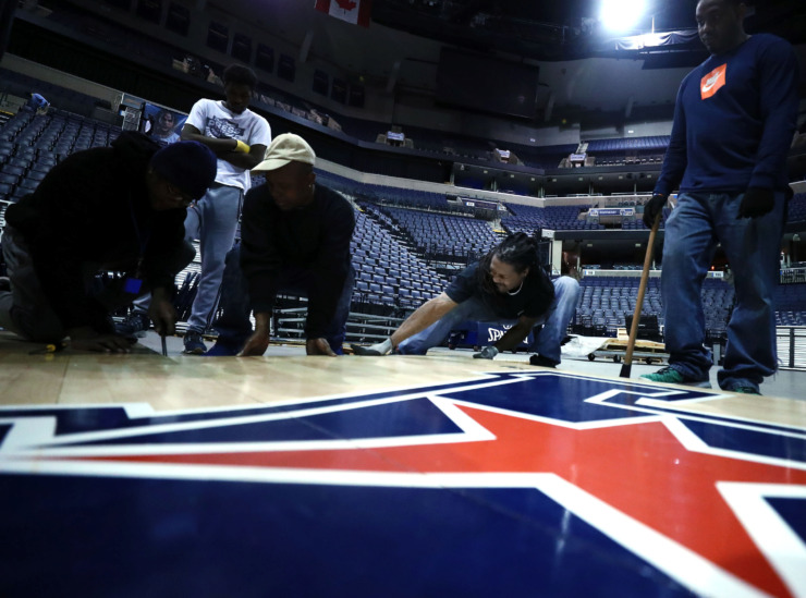 <strong>Joseph Woods (center), a contractor for the conversion team at the FedExForum, installs the AAC Tournament court with some help from his co-workers at the FedEx Forum. The University of Memphis will kick off their tournament schedule playing Tulane on Thursday, March 14.</strong> (Houston Cofield/Daily Memphian)
