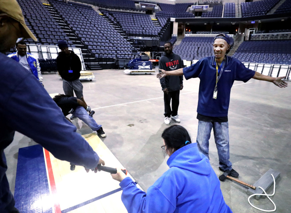 <strong>Derek Polk (right), a member of the conversions team at the FedExForum, laughs with a co-worker as they work on installing the court for the upcoming AAC Tournament. The University of Memphis will kick off their tournament schedule playing Tulane on Thursday, March 14.</strong> (Houston Cofield/Daily Memphian)