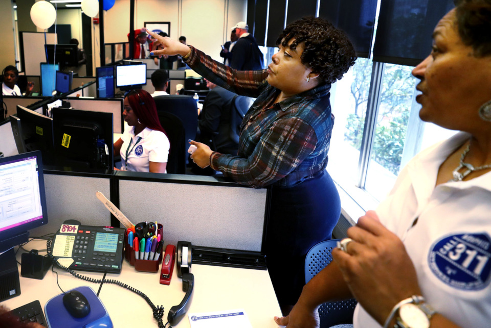 <strong>Candice Grose (left), who works in engagement and branding for the City of Memphis, talks with 311 call center supervisor Carolyn Malone (right), on Monday, March 11, at the annual <span>&ldquo;</span>311 Day.<span>&rdquo;</span> The event was hosted in the call center at City Hall to promote the service that handles problems for citizens daily.</strong> (Houston Cofield/Daily Memphian)