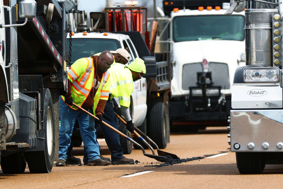 <strong>Ray Johnson (from left), Andre Smith and Bobby Boyd, all Tennessee Department of Transportation employees, fill potholes along U.S. 70 in Arlington. This week Arlington approved a $1.1 million construction contract for the widening of U.S. 70.</strong> (Houston Cofield/Daily Memphian)