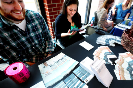 <strong>Blake Barnes (left), a marketing specialist for the University of Tennessee Health Science Center, and Irina Ollar (right), senior project manager for the university, hand out informational brochures to attendees of the Shelby County Opioid Summit on Thursday, March 14, 2019, at the University of Memphis.</strong> (Houston Cofield/Daily Memphian)
