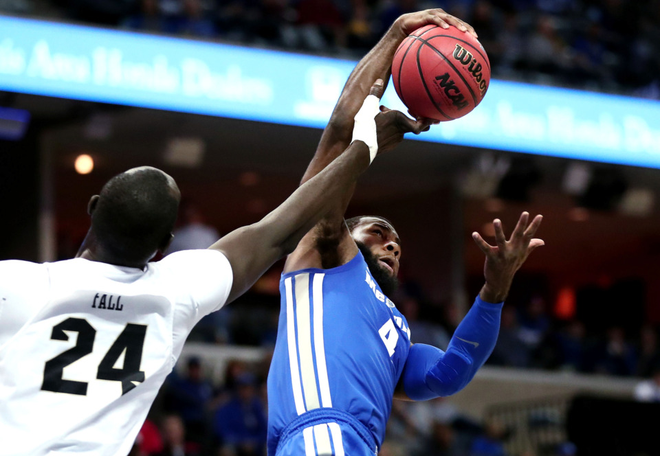 "<strong>University of Memphis forward Raynere Thornton (4) pulls down a rebound against University of Central Florida center Tacko Fall (24)&nbsp;</strong><span class=""s1""><strong>during an AAC tournament game against UCF on Friday, March 15, 2019, at FedExForum in Memphis. </strong>(Houston Cofield/Daily Memphian)</span>"