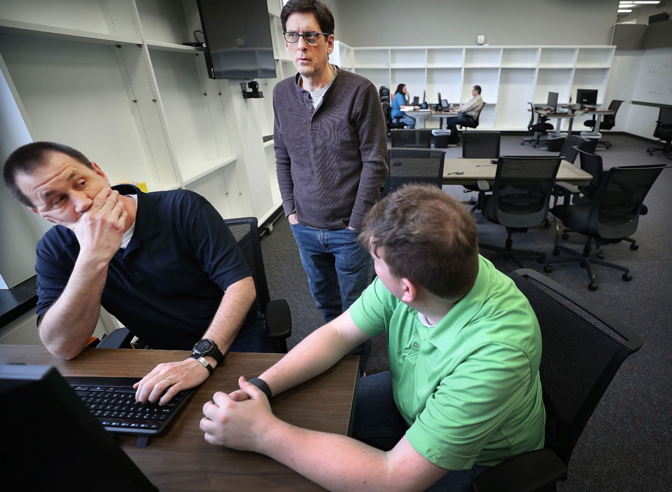 <strong>Software engineers James Carpenter (left), Robbie Hughes and David Sossaman with Green Mountain team up on a routing issue as they get settled into their new office on March 13, 2019. Green Mountain is the latest technology company and will be the largest tenant at the University of Memphis' new research park in the former Highland Library.</strong> (Jim Weber/Daily Memphian)
