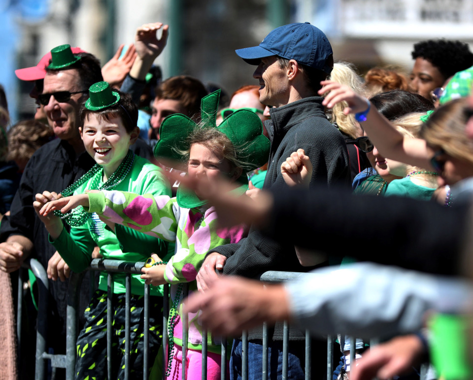 <strong>Tyler Gibson (left), 10, snags some beads from a parade float along Beale Street during the annual St. Patrick's Day Parade. Thousands of locals and tourists gathered along the iconic Downtown Memphis street on Saturday, March 16, 2019, to celebrate the holiday.</strong> (Houston Cofield/Daily Memphian)