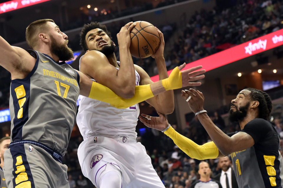 <strong>Minnesota Timberwolves center Karl-Anthony Towns (center) struggles for control of the ball against Memphis Grizzlies center Jonas Valanciunas (17) and guard Mike Conley (right) in an NBA game Saturday, March 23, 2019, in Memphis.</strong> (AP Photo/Brandon Dill)