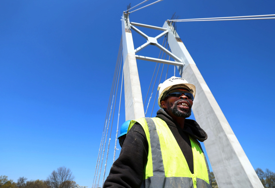 <strong>Alvin Griggs, a general contractor for Flintco., cleans up a job site with co-workers on top of the new pedestrian bridge over Southern Ave. on the University of Memphis campus. The $33 million project which includes a bridge, parking garage, walking paths, and an outdoor amphitheatre is set to be finished for the 2019 fall semester.</strong> (Houston Cofield/Daily Memphian)