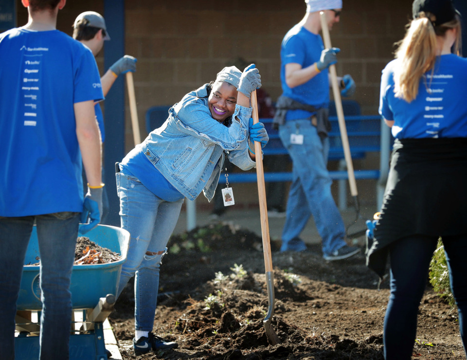 <strong>Andrea Williams takes a break from landscaping as ServiceMaster employees help out at Kirby High School on Thursday, March 28, during Spring Clean '19, a citywide beautification project to help local schools tidy up their properties.</strong>&nbsp;<strong>ServiceMaster deployed an estimated 350 employees to the SCS campuses for landscaping, painting and other cleanup efforts. Volunteers also went to Ida B. Wells Academy, Booker T. Washington High School and Riverview Middle School.</strong> (Jim Weber/Daily Memphian)