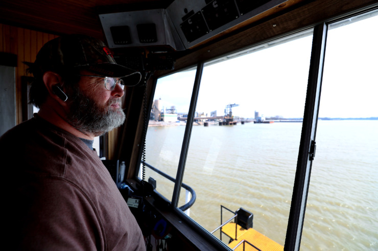 <strong>Captain Robert Smith, a boat captain for Wepfer Marine, maneuvers a riverboat tug along McKellar Lake to attach it to a barge. Smith has been with Wepfer for 20 years and traverses the river on a daily basis.</strong> (Houston Cofield/Daily Memphian)