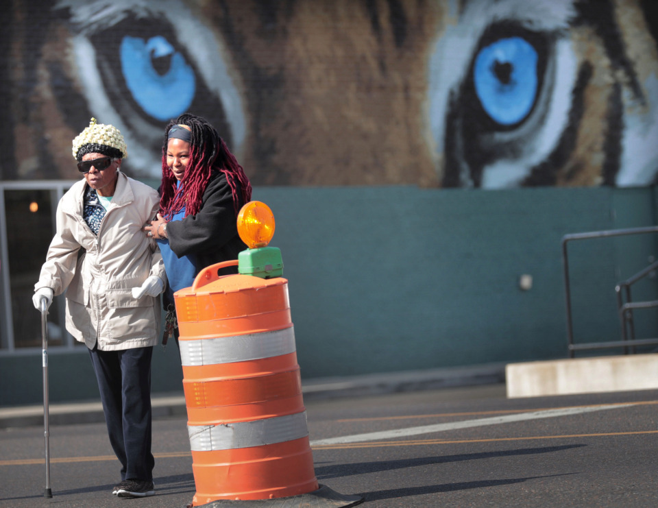 <strong>Tracey Brown helps Doris Carter across the street April 3, 2019, near a construction project at Highland and Walker to build a crosswalk for pedestrians headed to shops along the Highland Strip.</strong> (Jim Weber/Daily Memphian)