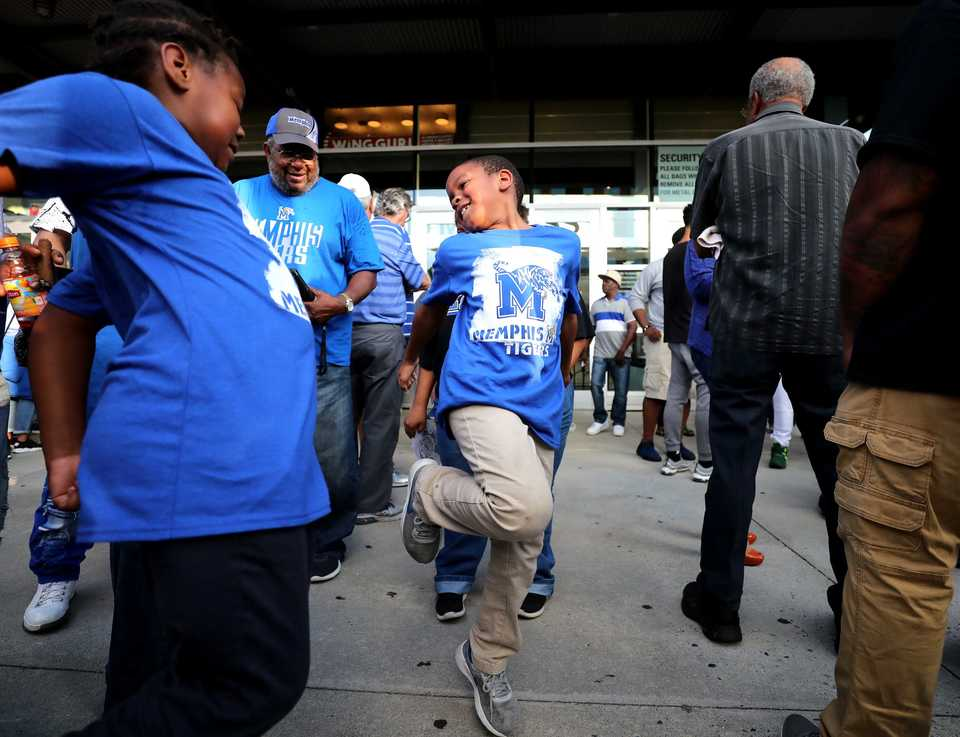 <strong>Jayson Coleman (center), 8, dances outside FedExForum before the beginning of Memphis Madness Thursday, Oct. 4. Tiger fans gathered at the forum for music and entertainment for the event.</strong> (Houston Cofield/Daily Memphian)