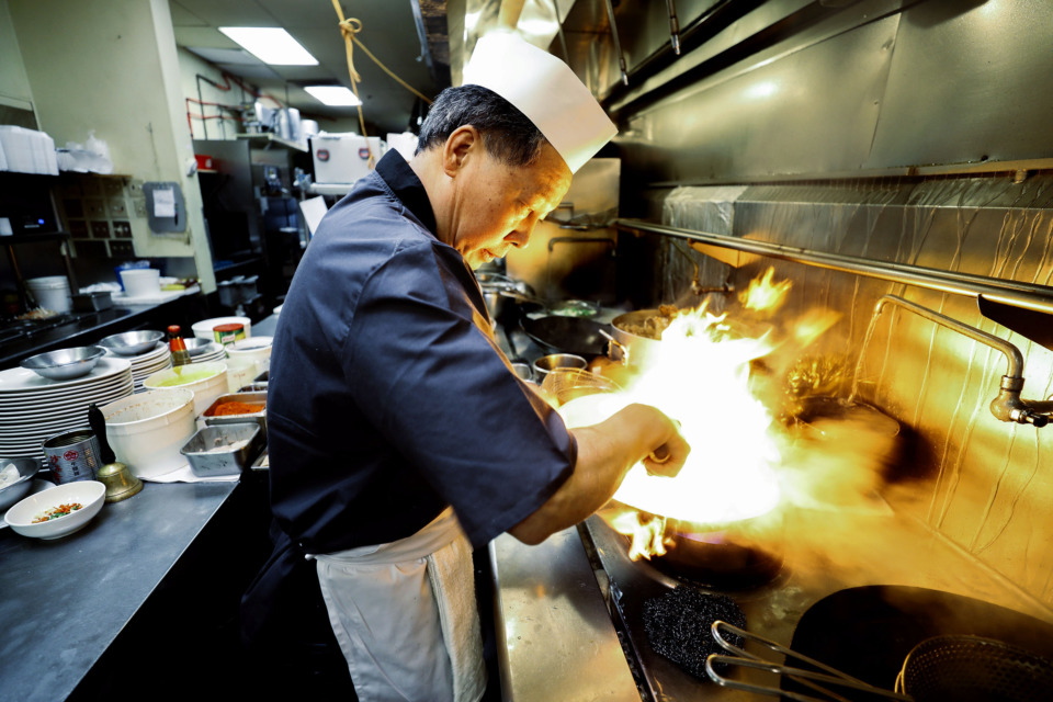 <strong>Chef and owner of New Asia in Germantown, Yong Hu, prepares one of his signature dishes, maggi beef, inside the restaurant's kitchen.</strong> (Houston Cofield/Daily Memphian)