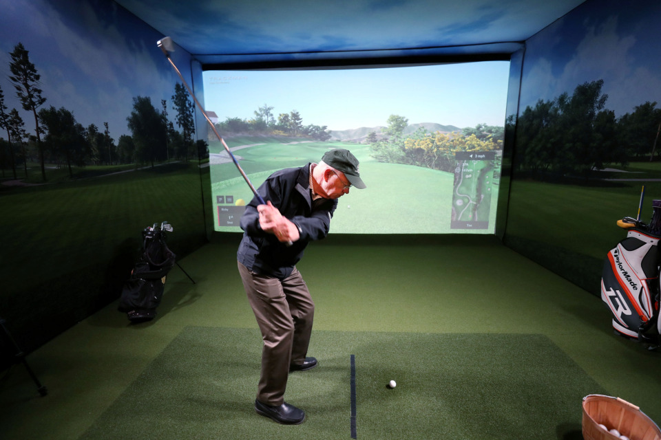 <strong>Bill Powell, co-owner of the building that houses The Yard, tees off in the fitness facility's virtual golf course. The room is equipped with camera tracking technology that can give golfers precise data relating to their golf swing which can be a valuable training asset for pros and amatuers alike.</strong> (Houston Cofield/Daily Memphian)