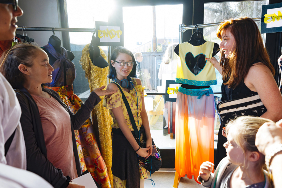 <strong>Memphis Fashion Week Emerging Designer Showcase offers an opportunity for designers to display their work. Visitors listen Friday at Crosstown Brewing Co. as Overton High School teacher Jeannine LaBate (right) discusses a teen category submission by her freshman student Breanna Mansel. </strong>(Ziggy Tucker/Special to The Daily Memphian)