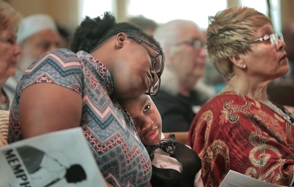 <strong>Reuben Davidson listens with his sister Saniyah Bennett-Rauls to an opening hymn during a multicultural Memphis Cares 2 event at St. John's United Methodist Church on Sunday, April 7. The 9-year-old was one of nearly a dozen speakers at the event. The original Memphis Cares gathering was held at Crump Stadium three days after the assassination of Dr. Martin Luther King Jr.</strong> (Jim Weber/Daily Memphian)