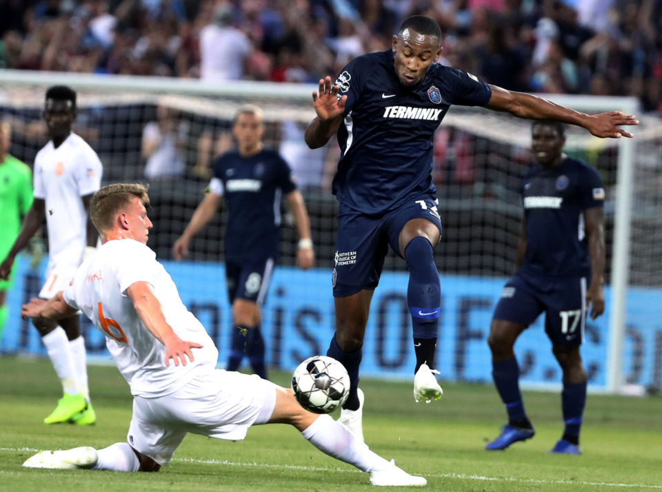 <strong>Memphis 901 FC forward Rashawn Dally (14) hurdles over Atlanta United 2 midfielder Laurence Wyke (6) during a match against Atlanta United 2 on Wednesday, April 10, 2019. Memphis controlled the game but ended the night with its third loss.</strong>&nbsp;(Houston Cofield/Daily Memphian)