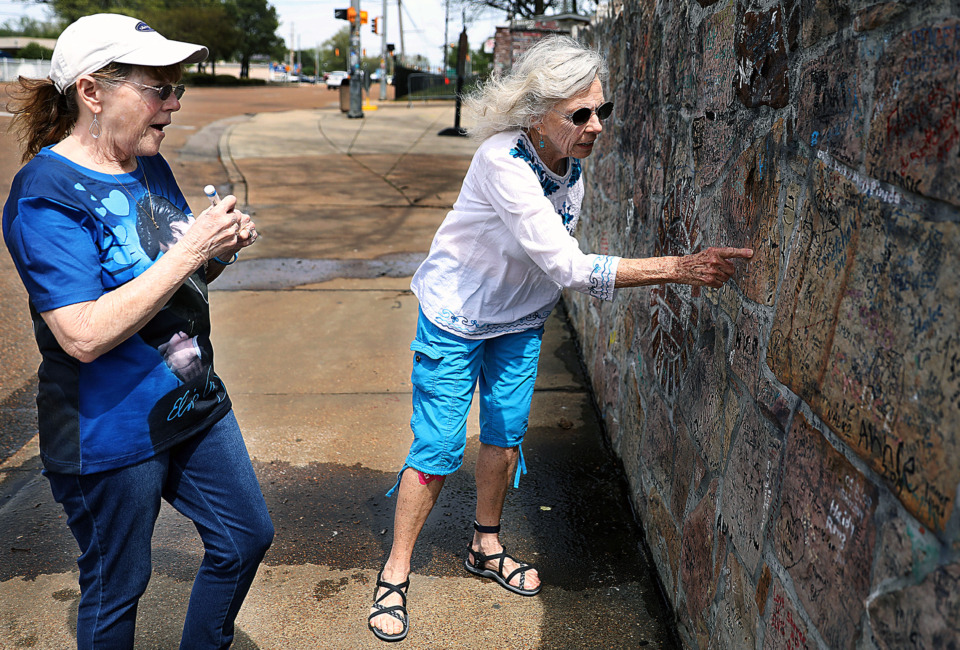 <strong>Joan March (right) finds a place on the wall for her friend Nadine Wilson to sign outside Graceland while visiting Memphis on Thursday, April 11, 2019. A $43 million streetscape project on Elvis Presley Boulevard looks to increase business along Whitehaven's main thoroughfare.</strong> (Patrick Lantrip/Daily Memphian)