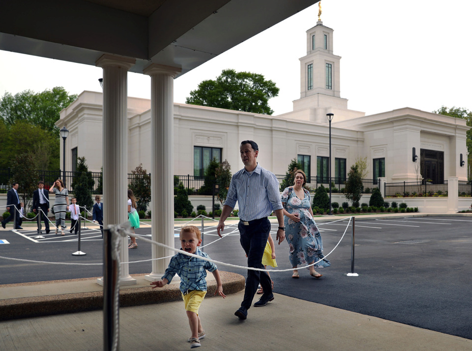 <strong>An excited young Dean Hubbard runs in front of his father, Chris, and mother, Kristen, after a tour of the Church of Jesus Christ of Latter-day Saints' Bartlett temple, which recently underwent an extensive renovation.</strong> (Patrick Lantrip/Daily Memphian)