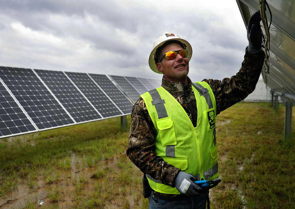 <strong>Patrick Glover with McCarthy Building Co. performs wire maintenance on Friday, April 19 to a few of the thousands of solar panels at the Millington Solar Farm, which is managed by Silicon Ranch Corp. through a public-private partnership.</strong> (Patrick Lantrip/Daily Memphian)