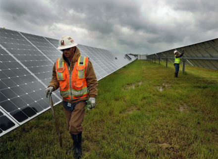 <strong>David Sherrock picks up storm-strewn debris from the Millington Solar Farm while co-worker Patrick Glover fixes some lose wires in the background Friday, April 19.</strong> (Patrick Lantrip/Daily Memphian)