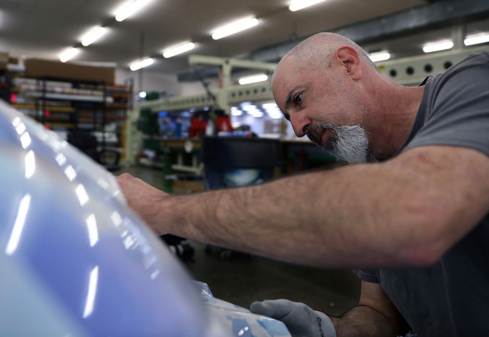 <strong>Mark Hall wraps a golf cart with a custom print for a client at LSI Graphic's Bartlett headquarters Monday, April 15.</strong> (Patrick Lantrip/Daily Memphian)