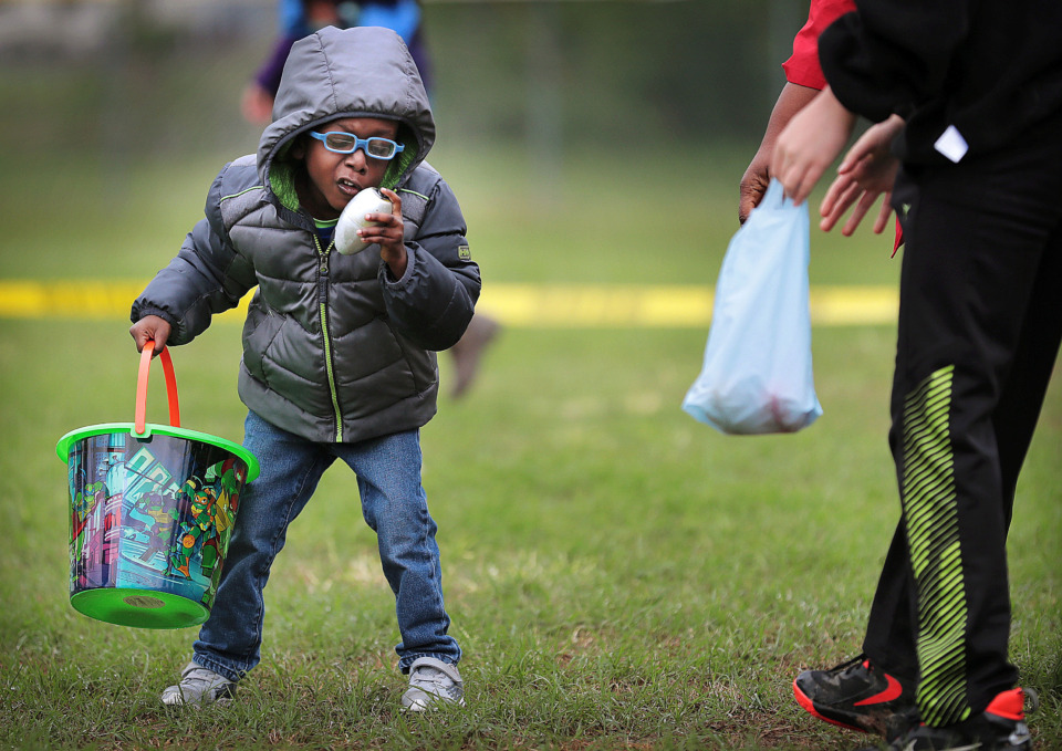 <strong>Bryson Taylor, 5, who suffers from near blindness due to cataracts, puzzles out how to turn off a beeping egg before competing hunters hone in on the sound during an Easter egg hunt for the blind hosted by the Shelby County Sheriff's Office at Willow Park on April 19, 2019. Some sight-impaired kids and adults got to participate in a hunt for the first time, searching the park for beeping plastic eggs that they turned in later for treats.</strong> (Jim Weber/Daily Memphian)