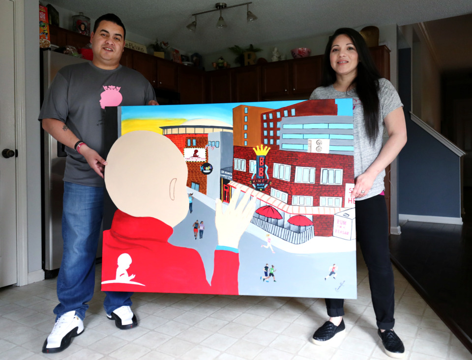 <strong>Enrique Ramirez surprised his wife, Leticia Ramirez, with a painting created for last year's student art contest at the Memphis Internatioanl Airport. The painting was made by a Kingsbury High School student, and depicts the couple's late daughter Arianna Ramirez when she was a patient at St. Jude.</strong> (Houston Cofield/Daily Memphian)