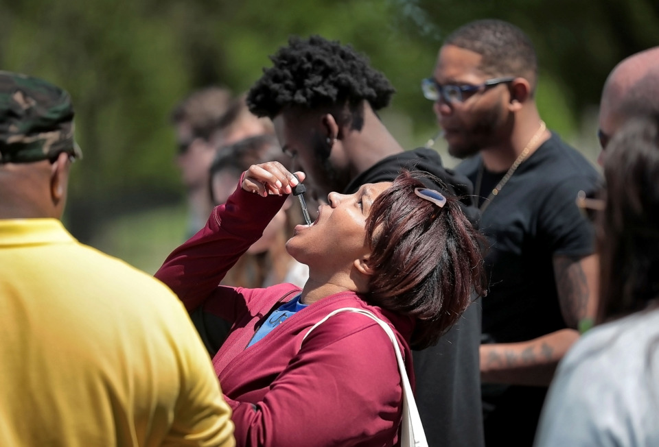 <strong>Iseashia Thomas samples CBD oil, a legal form of marijuana that she hopes will help cure her migraine headaches, during the first Mid-South Hemp Fest at Overton Park on April 20, 2019. </strong>(Jim Weber/Daily Memphian)