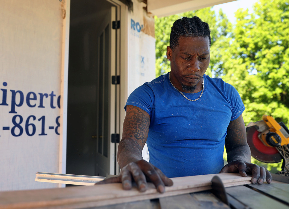 <strong>Devon Varnedoe cuts a piece of flooring while working on the upstairs of 645 Adams, which, like the recently completed house next door, will serve as an upscale Airbnb rental.</strong> (Patrick Lantrip/Daily Memphian)
