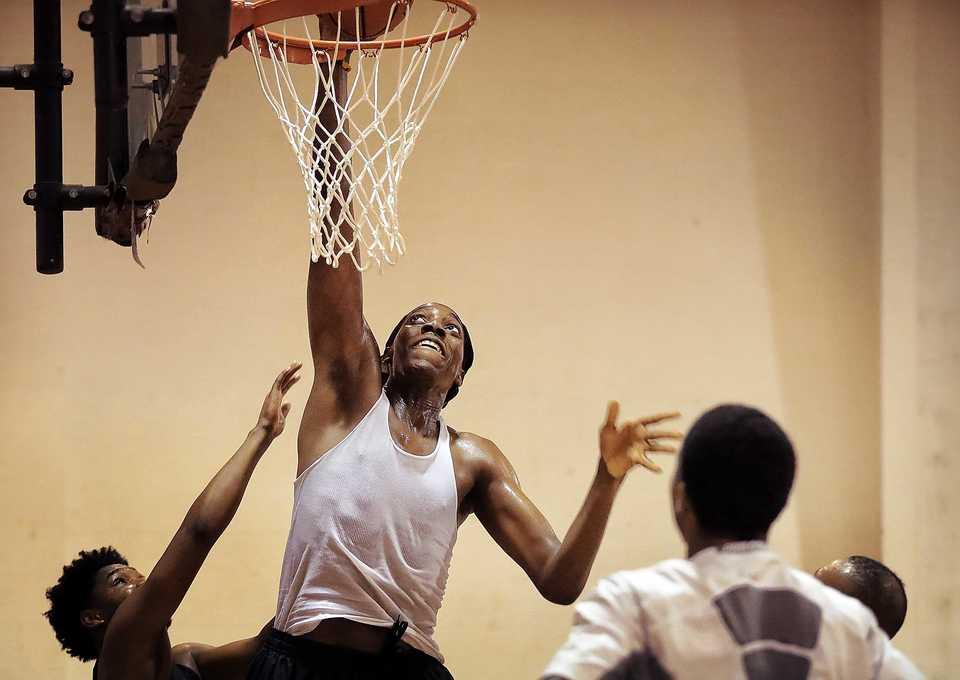 "<strong>Emmanuel Umoffia goes up for a dunk as he and fellow players with Eric ""Cowboy"" Robinson's Mid South Prep Academy basketball team practice at the Faith Community AME Church gym in Southaven in September. The team is a mix of high school players from Robinson's training program and prep school that will play other prep schools and junior colleges.</strong> (Jim Weber/Daily Memphian)"