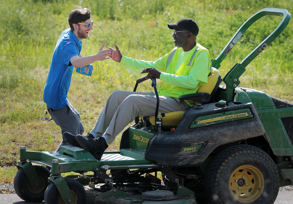 <strong>Ronnie Humphrey (right) with the Memphis parks department gets a high five from the Wolf River Conservancy's Nick Wigins as groups of volunteers help spruce up a new section of the Wolf River Greenway in Raleigh on April 24, 2019 in preparation for a grand opening Saturday.</strong> (Jim Weber/Daily Memphian)
