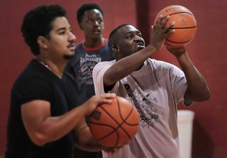 "<strong>Eric ""Cowboy"" Robinson (right) shoots baskets with his team, the Mid South Prep Academy, at the Faith Community AME Church gym in Southaven in September. The team is a mix of high school players from Robinson's training program and prep school that will play other prep schools and junior colleges.</strong> (Jim Weber/Daily Memphian)"