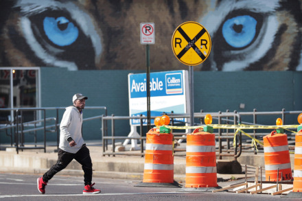 <strong>Antonio Shields crosses the street on his way to work in early April near an ongoing construction project at Highland and Walker to build a crosswalk for pedestrians headed to shops along the Highland Strip.</strong> (Jim Weber/Daily Memphian)