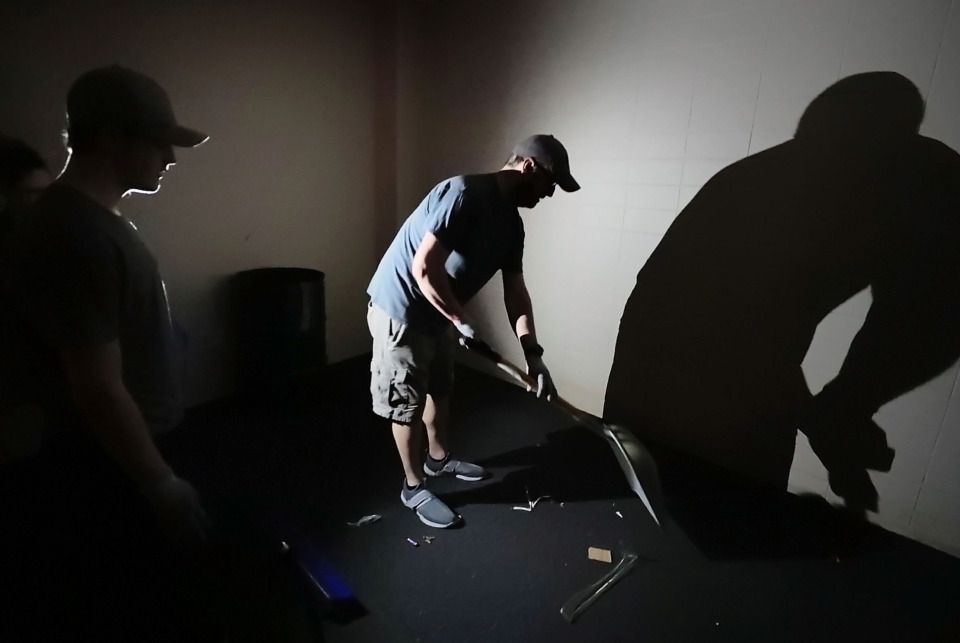 <strong>Brian George and his family clean up glass from one of the offices at the Mid-South Coliseum. They are among the volunteers who pitched in Saturday, April 27, 2019, to remove debris from the historic arena. </strong>(Jim Weber/Daily Memphian)