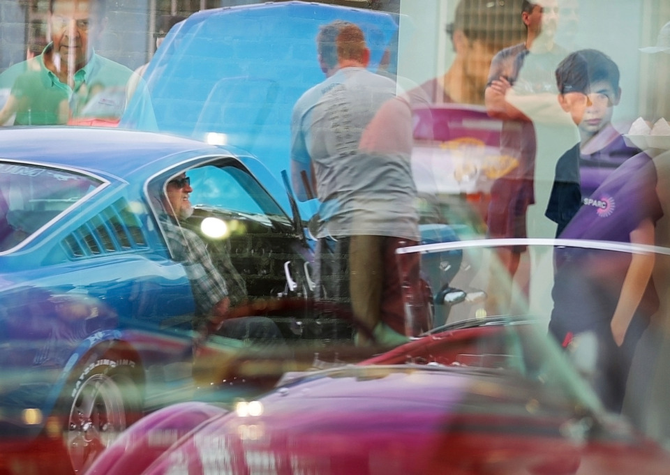 <strong>Car enthusiasts are reflected in the window of the&nbsp;<span>Edge Motor Museum</span> where Chris Oswalt (center) and his son Jackson Oswalt, 14, check out a 1959 Cadillac on display during a block party to celebrate the opening of the Edge Automotive Museum on Saturday, April 27, 2019. The Edge District in Downtown Memphis has a rich history as a car repair and dealership district.</strong> (Jim Weber/Daily Memphian)