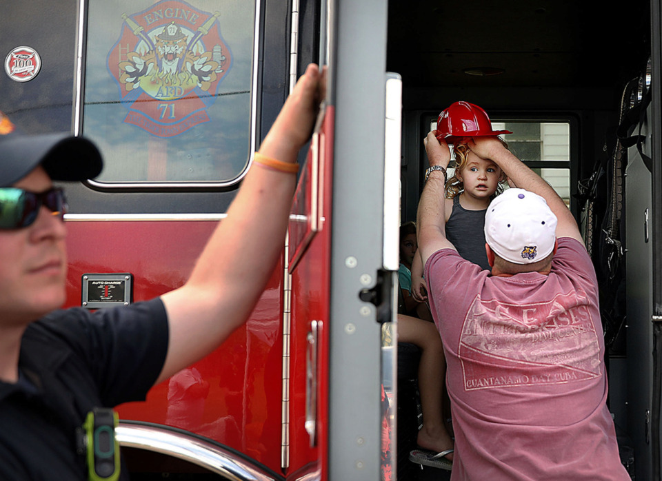 <strong>Arlington firefighter Cody Conley holds the door for Philip Huntington as he adjusts his daughter Sarah&rsquo;s toy firefighter&rsquo;s helmet during the town's 29th annual spring festival, Arlington in April.&nbsp;Thousands turned out on Saturday, April 27, in Arlington&rsquo;s historic Depot Square for the event.</strong> (Patrick Lantrip/Daily Memphian)