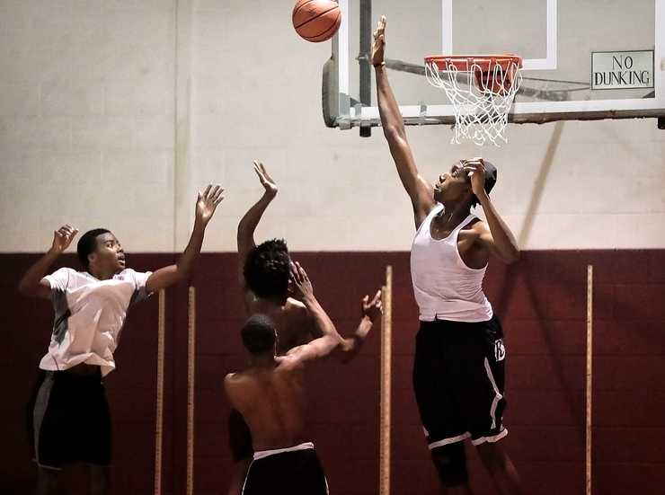 <strong>Sports Academy basketball team member Jaylin Scott (center) goes in for a layup under pressure by Tre'vion Jackson (right) during practice at the Faith Community AME Church gym in Southaven on September 20, 2018. The team is a mix of high school aged players from Robinson's training program and prep school that will play other prep schools and junior colleges.</strong> (Jim Weber/Daily Memphian)