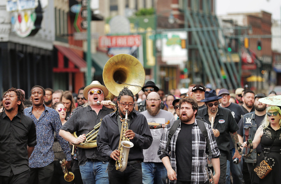 "<strong>Local musicians, fans, friends and family sing ""When the Saints Go Marching In"" as they march in a Beale Street funeral procession to honor Memphis musician Omar Higgins. A crowd led Higgins' casket on April 30, 2019, second-line style to Clayborn Temple for a visitation and funeral service.</strong> (Jim Weber/Daily Memphian)"