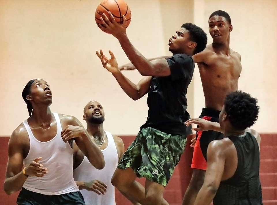 <strong>Mid South Prep Academy basketball team member Jaylin Scott (center) goes in for a layup under pressure by Tre'vion Jackson (right) during practice at the Faith Community AME Church gym in Southaven in September.</strong> (Jim Weber/Daily Memphian)
