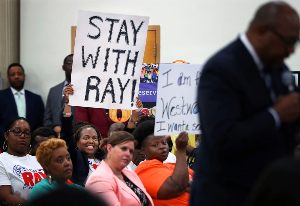 <strong>Melanie G. Wade-Simpson (left) lifts a sign urging the Shelby County Schools board to hire interim Superintendent Joris Ray on a permanent basis Tuesday, April 30, 2019, while Teresena Catron-Wright holds up a sign calling for a national search. The board unanimously voted to hire Ray and forgo a search. </strong>
