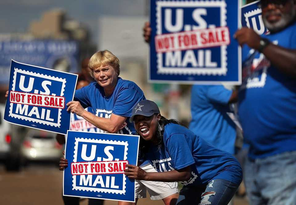 <strong>Postal workers Debbie Gore (left) and Betty Stricklen try to get the attention of passing cars while protesting in front of the Main Post Office on October 8, 2018. Memphis postal workers rallied in opposition to President Donald Trump's proposal to privatize the Postal Service.</strong> (Jim Weber/Daily Memphian)