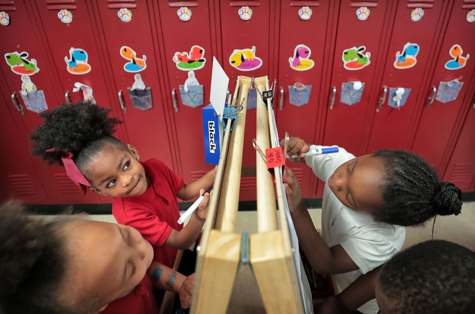 <strong>Madison Clark (left), Ayanna Hughes, La'kiya Carr and Jaylen King work at an easel where they color their reading assignment in Thomas Denson's Pre-K class at Cherokee Elementary School. More than three in four Shelby County elementary students, and four in five middle and high school students, read below grade level.</strong>&nbsp;(Jim Weber/Daily Memphian)