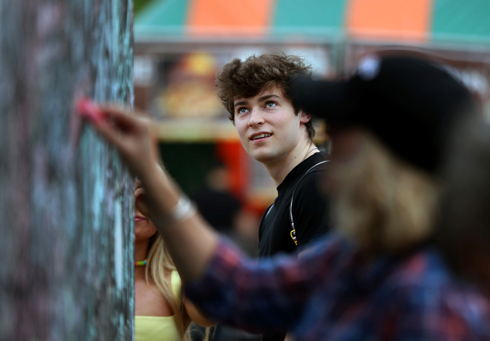 <strong>Nick Mortoza eyes a wall full of chalk signatures at the Beale Street Music Festival on Friday, May 3, 2019, in Tom Lee Park. The communal art wall was provided by the Downtown Memphis Commission.</strong> (Patrick Lantrip/Daily Memphian)